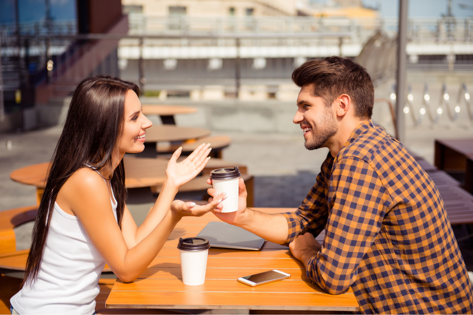 a man and a woman sit outdoors and talk