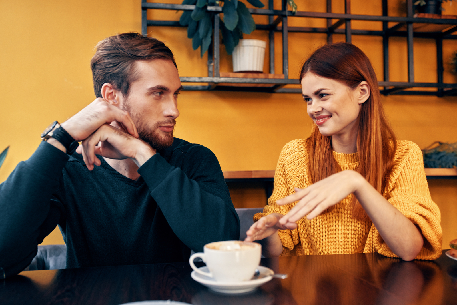 a man and a woman sitting at a table having coffee talking