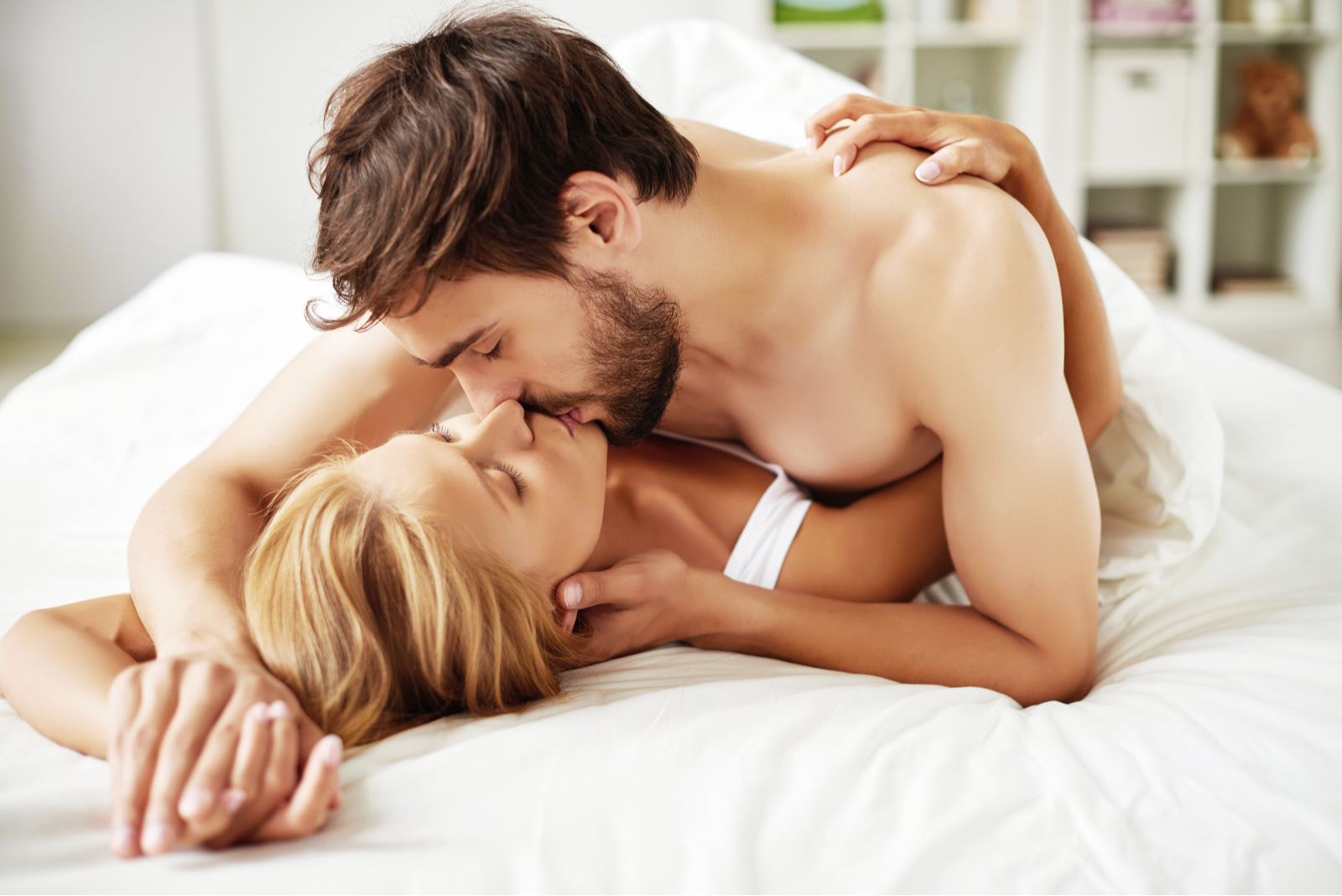 a man kisses a woman in bed