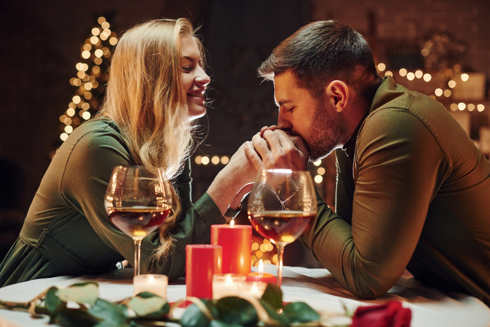 a man kisses a woman's hands as they sit at a table