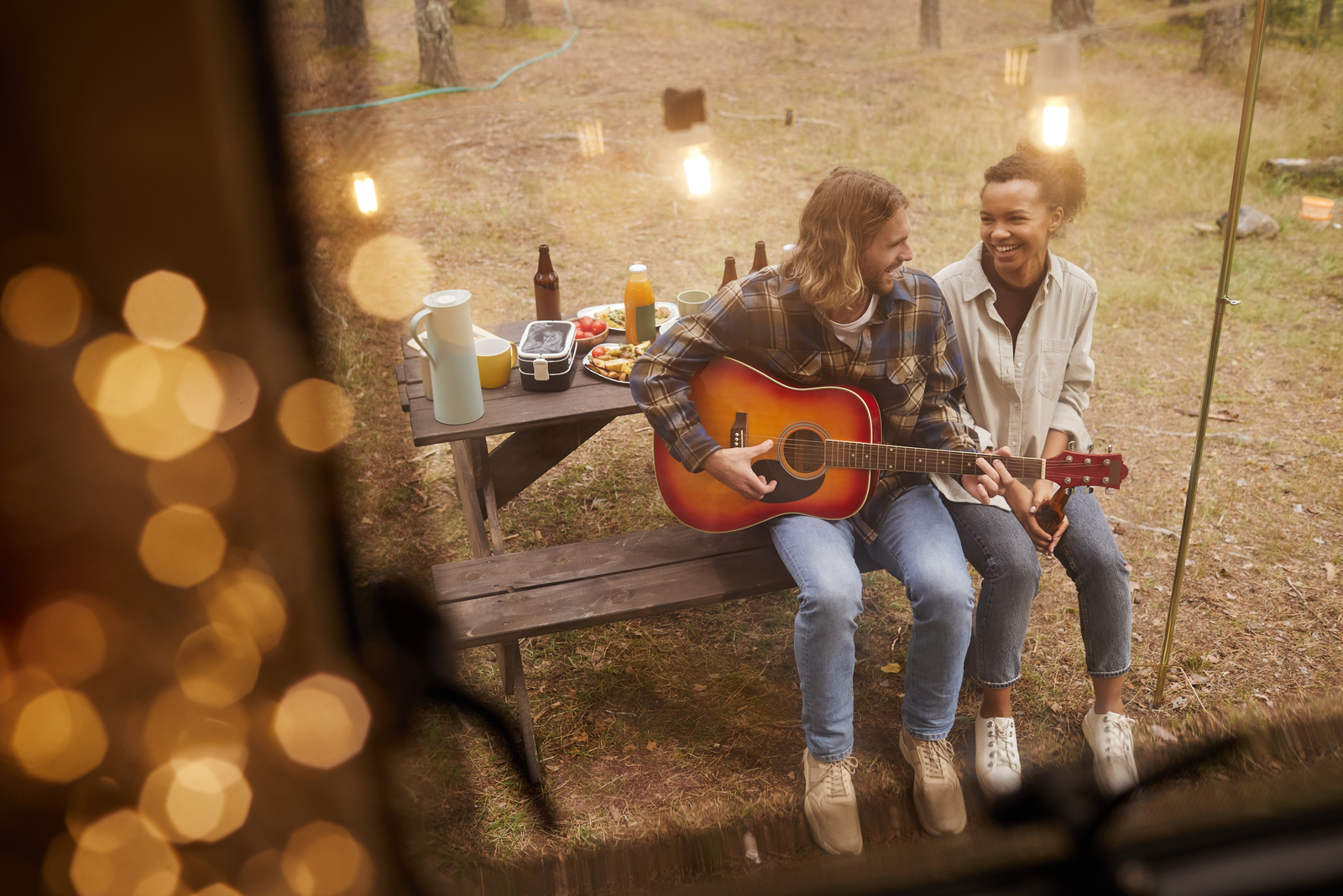 a man playing guitar a woman smiling sits next to him on a bench