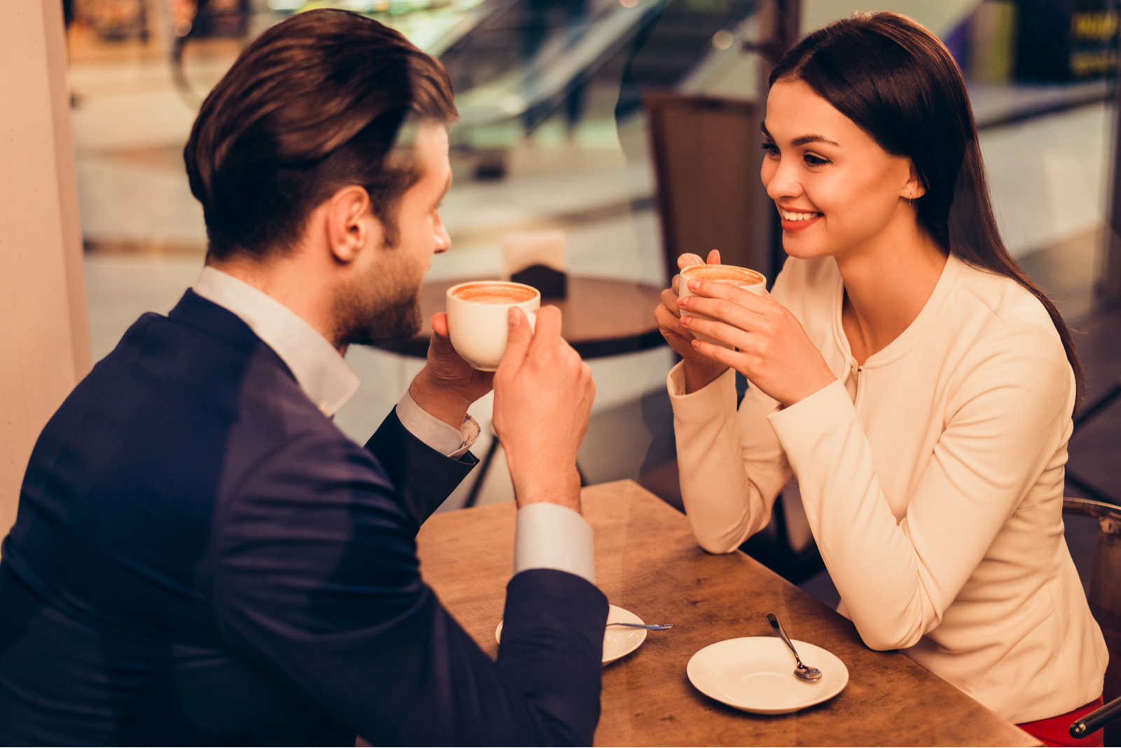 a smiling loving couple sitting at a table drinking coffee
