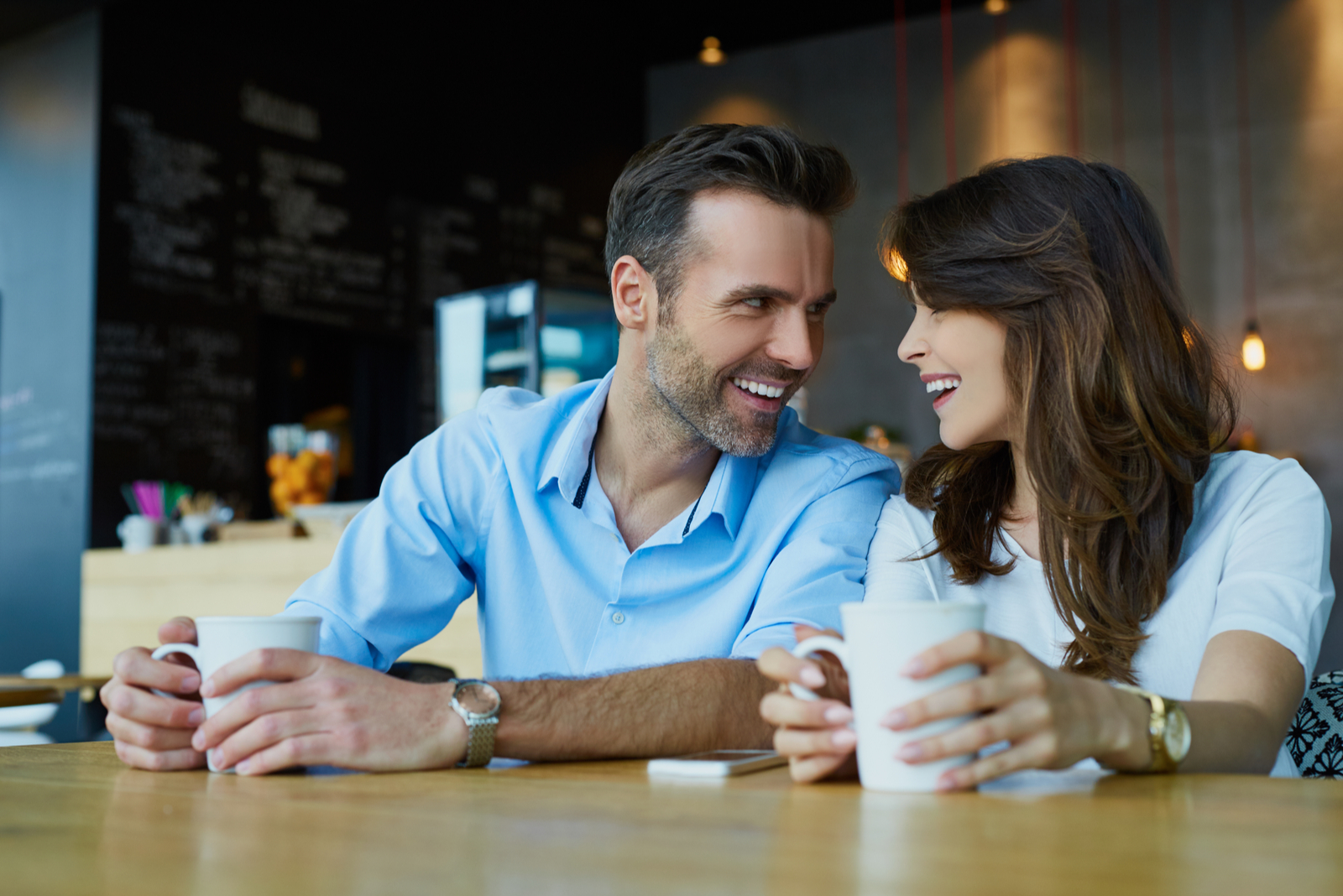 a smiling man and woman sit at a table and talk