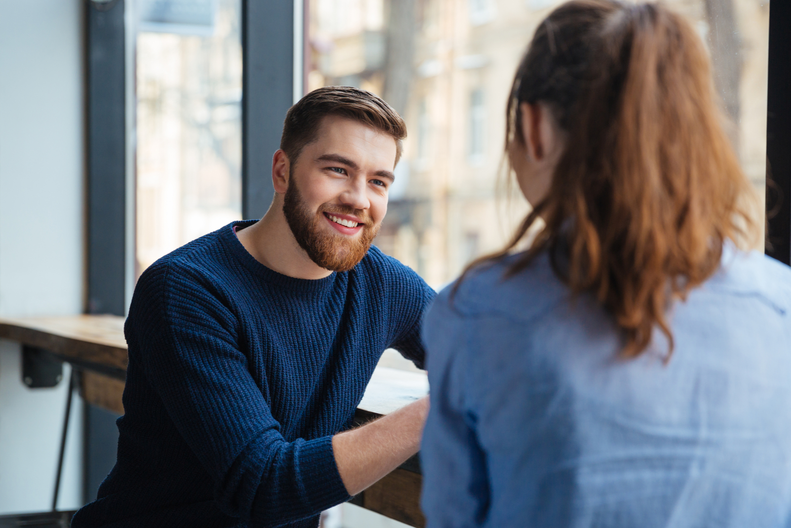 a smiling man talking to a woman