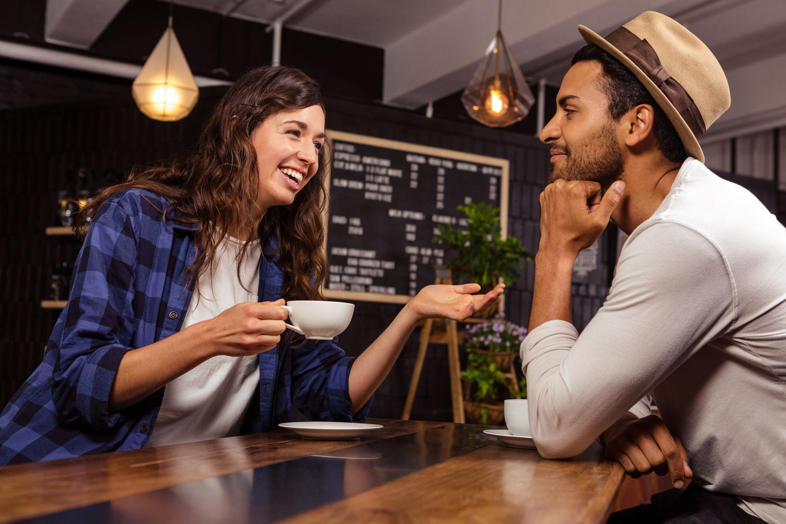 a smiling woman holding a cup of coffee and talking to a man