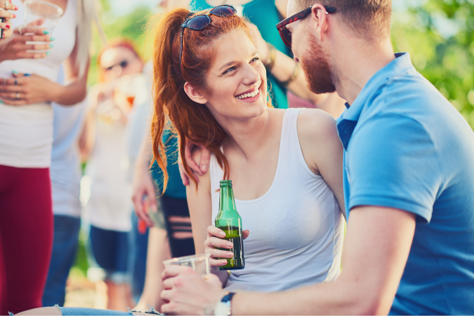 a smiling woman holds a beer in her hand and talks to a man