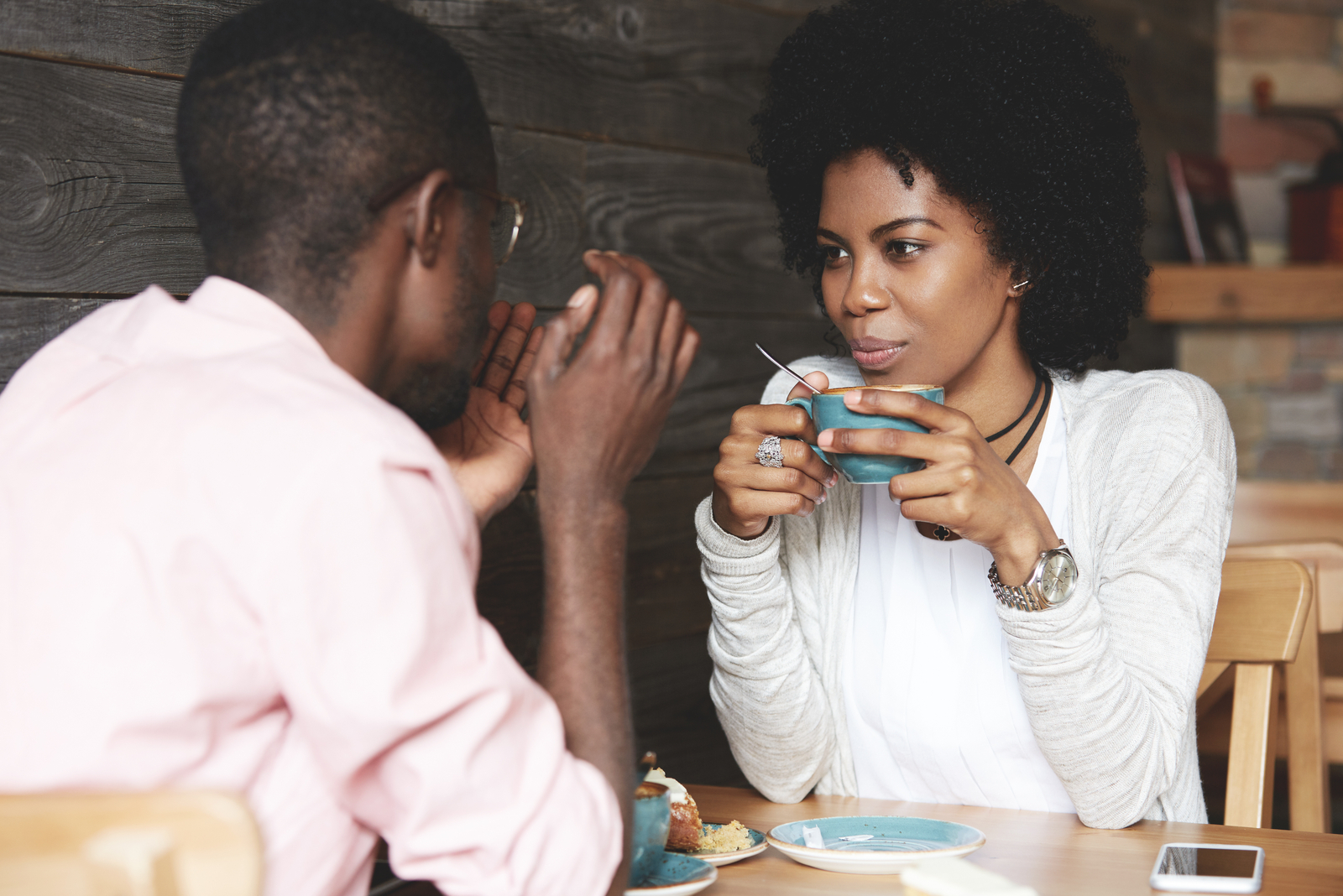 a woman with frizzy hair drinks coffee and talks to a man