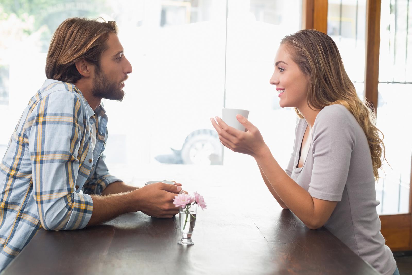 smiling couple having coffee talking